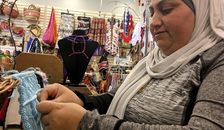 Former Iraqi refugee Nadeen Yousef creates hand crafts to sell at the West Side Bazaar, where refugees sell clothes, crafts and food, on Friday, Sept. 28, 2018, in Buffalo, N.Y. Thousands of refugees have settled in Buffalo in recent years even as others have left the city. Some locals worry that the Trump administration's policies reducing the numbers of new arrivals will harm the city's economy. (AP Photo/ Michael Hill)