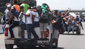 Central American migrants making their way to the U.S. cling to the trucks of drivers who offered them free rides, as they arrive to Tapachula, Mexico, Sunday, Oct. 21, 2018. Despite Mexican efforts to stop them at the Guatemala-Mexico border, about 5,000 Central American migrants resumed their advance toward the U.S. border Sunday in southern Mexico. Associated Press photo