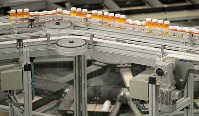 In this July 10, 2018, file photo bottles of medicine ride on a belt at the Express Scripts mail-in pharmacy warehouse in Florence, N.J. On Monday, Oct. 15, the industry's largest trade group announced that dozens of drugmakers will start disclosing the prices for U.S. prescription drugs advertised on TV. The prices won't actually be shown in the TV commercials but the advertisement will include a website where the list price will be posted. (AP Photo/Julio Cortez, File)