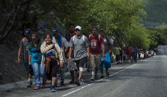 Honduras migrants walk to the U.S as they approach Zacapa, about 70 miles northeast of Guatemala City, Wednesday, Oct. 24, 2018. This new group of a few hundred Honduran migrants are behind the first group that has swelled to thousands and is currently traveling through Mexico. (AP Photo/Oliver de Ros)