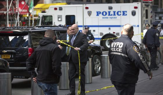 Detectives put up police lines after NYPD personnel removed an explosive device from Time Warner Center Wednesday, Oct. 24, 2018, in New York. Other packages were sent to the offices of Gov. Andrew Cuomo and to the home of President Bill Clinton. (AP Photo/Kevin Hagen).