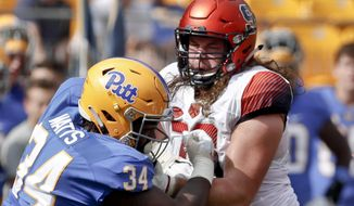 "FILE--In this Oct. 6, 2018, file photo, Syracuse offensive lineman Koda Martin, right, blocks Pittsburgh defensive lineman Amir Watts (34) during an NCAA football game in Pittsburgh. Martin and  Pittsburgh safety Dennis Briggs didn't want to wait until after college to get married. So they didn't. One of the factors that helped them take the plunge: the financial buffer provided by the NCAA's ""cost of attendance"" provision. (AP Photo/Keith Srakocic, File)"