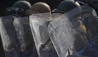 Indian police men use their shields during clashes with Kashmiri protesters in Srinagar, India, Wednesday, Oct. 24, 2018. Police say government forces have killed two rebels during a gunbattle in the outskirts of disputed Kashmir's main city, sparking violent anti-India protests by residents. (AP Photo/Dar Yasin)