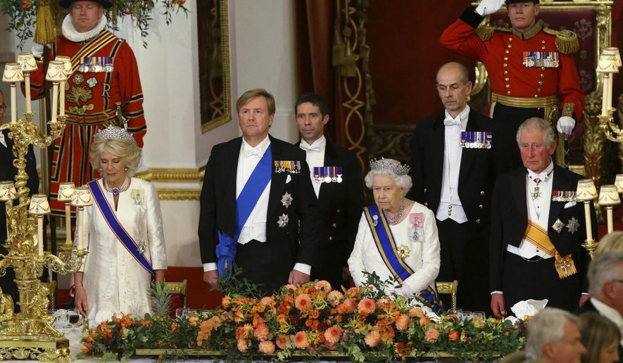 Britain's Queen Elizabeth II, King Willem-Alexander of the Netherlands, center left, stand during a State Banquet at Buckingham Palace, London, Tuesday Oct. 23, 2018. Dutch King Willem-Alexander and Queen Maxima are on a two-day State Visit to Britain. (Yui Mok/Pool via AP)
