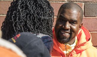 """Chicago mayoral candidate Amara Enyia, left, chats with Kanye West during a """"pull-up"""" rally Tuesday, Oct. 23, 2018, in Chicago. (Ashlee Rezin/Chicago Sun-Times via AP)"""