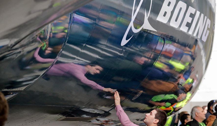 FILE - In this Feb. 5, 2018, file photo, Boeing worker Paul Covaci reaches out to touch a Boeing 737 MAX 7, the newest version of Boeing's fastest-selling airplane, during a debut for employees and media of the new jet in Renton, Wash. Boeing Co. reports earnings Wednesday, Oct. 24. (AP Photo/Elaine Thompson, File)