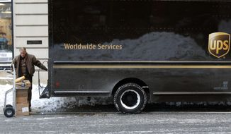 FILE- In this Jan. 5, 2018, photo, a UPS delivery driver loads his cart with packages from his truck, in Boston. UPS Inc. reports earnings Wednesday, Oct. 24. (AP Photo/Bill Sikes, File)