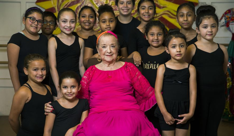 In this Saturday, Aug. 18, 2018 photo, Anita N. Martinez poses for a photo with young students at her ballet folklorico studio in Dallas. (Ashley Landis/The Dallas Morning News via AP)