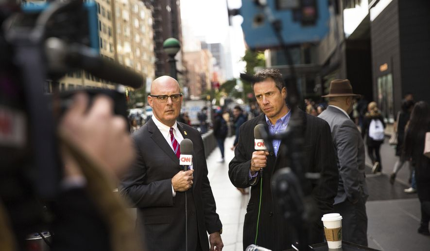CNN correspondents Jeff Gagliano and Chris Cuomo speak on air in front of the Time Warner Building, where NYPD personnel removed an explosive device Wednesday, Oct. 24, 2018, in New York. (AP Photo/Kevin Hagen).