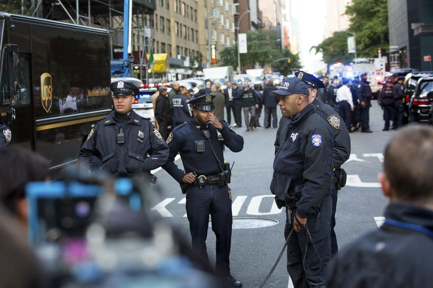 Officers watch over the scene outside the Time Warner Center on Wednesday, Oct. 24, 2018, in New York. Law enforcement officials say a suspicious package that prompted an evacuation of CNN's offices is believed to contain a pipe bomb. (AP Photo/Kevin Hagen)