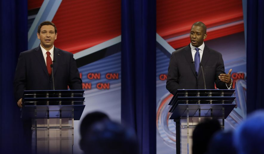 FILE - In this Sunday, Oct. 21, 2018 file photo, Republican gubernatorial candidate Ron DeSantis, left and Democratic gubernatorial candidate Andrew Gillum, right, speak during a CNN debate in Tampa, Fla. The candidates for Florida governor are scheduled to debate for the second and final time, three days after their first testy encounter. DeSantis and Gillum will meet Wednesday night, Oct. 24, 2018, at a community college near Fort Lauderdale. (AP Photo/Chris O'Meara, File)