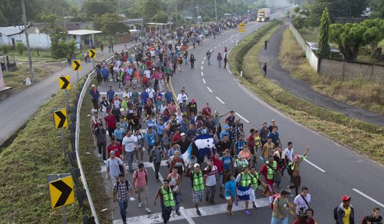 In this Oct. 21, 2018, photo, Central American migrants walking to the U.S. start their day departing Ciudad Hidalgo, Mexico. (AP Photo/Moises Castillo)