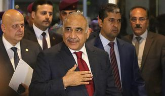 Prime Minister-designate Adel Abdul-Mahdi, center, arrives to the parliament building, in the heavily guarded Green Zone, in Baghdad, Iraq, Wednesday, Oct. 24, 2018.  Iraq's parliament is convening to vote on Prime Minister-designate Adel Abdul-Mahdi's ministry appointments, and the parliament must confirm the appointments for the government to be sworn in. (AP Photo/Hadi Mizban)