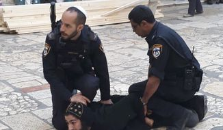 In this photo released by the Coptic Patriarchate, Israeli policemen arrest a Coptic priest outside the Church of the Holy Sepulcher in Jerusalem, Wednesday, Oct. 24, 2018. Police and Coptic priests wrangled on Wednesday outside a contested chapel at the Church of the Holy Sepulcher, where many Christians believe Jesus was crucified, buried and resurrected. The Copts were protesting the arrival of Israel Antiquities Authority restoration workers at the St. Michael the Archangel Chapel, which both Ethiopian and Egyptian Orthodox churches claim. (Coptic Patriarchate via AP)