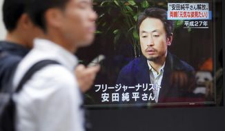 "Men walk past a TV screen showing a news program with an image of Japanese freelance journalist Jumpei Yasuda, Wednesday, Oct. 24, 2018 in Tokyo. A man believed to be Yasuda who disappeared three years ago in Syria has been released and is now in Turkey, a Japanese official said. Japanese characters at top right read: ""Jumpei Yasuda was released."" (AP Photo/Eugene Hoshiko)"