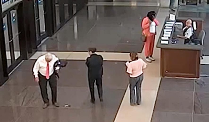 FILE - In this July 3, 2018, file photo from a surveillance video provided by the Cook County Sheriff's Office, Cook County Circuit Judge Joseph Claps, left, looks down at an object he allegedly dropped in the lobby of the Leighton Criminal Court Building in Chicago. Claps was charged with carrying a concealed weapon in a prohibited area. On Tuesday, Oct. 23, 2018, Claps was acquitted after a judge ruled the video did not prove the object that fell from Claps' jacket was a firearm. (Cook County Sheriff's Office via AP, File)
