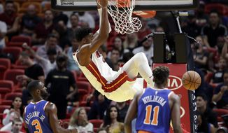 Miami Heat center Hassan Whiteside dunks over New York Knicks guard Tim Hardaway Jr. (3) and guard Frank Ntilikina (11) during the first half of an NBA basketball game, Wednesday, Oct. 24, 2018, in Miami. (AP Photo/Lynne Sladky)