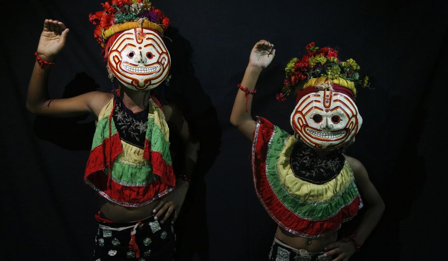 In this Sept. 23, 2018, photo, dancers pose for photographs wearing masks of god Kawancha in Kathmandu, Nepal.  For centuries, Nepal has celebrated the Indra Jatra festival of masked dancers, which officially begins the month-long festivities in the Hindu-dominated Himalyan nation. The dancers, who come from a variety of backgrounds, pull off this performance every year despite minimal financial support from the government and other sources, they say. (AP Photo/Niranjan Shrestha)
