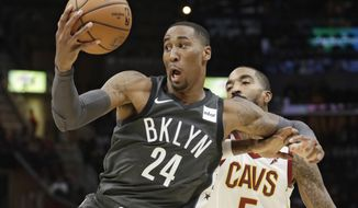 Brooklyn Nets' Rondae Hollis-Jefferson (24) grabs a pass against Cleveland Cavaliers' JR Smith (5) in the first half of an NBA basketball game, Wednesday, Oct. 24, 2018, in Cleveland. (AP Photo/Tony Dejak)