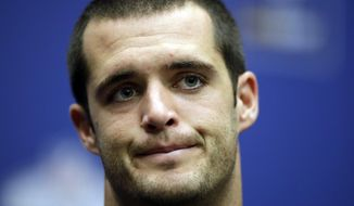 """FILE - In this Oct. 14, 2018 file photo Oakland Raiders quarterback Derek Carr (4) listens during a news conference after an NFL football game against Seattle Seahawks at Wembley stadium in London. Carr's No. 1 receiver has been traded just weeks after the Raiders dealt away another cornerstone player in Khalil Mack. Carr has just one win, has struggled to adjust to coach Jon Gruden's offense and taken more of a physical beating than he has at any time during his five-year career. As if that wasn't enough, he also has had to deal with reports that unidentified teammates have lost faith in him and his toughness has been questioned. """"I don't pay that any mind,"""" Carr said Wednesday, Oct. 24, 2018. (AP Photo/Matt Dunham, file)"""