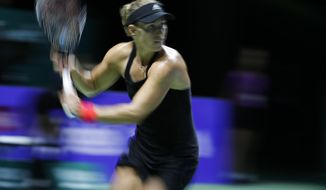 Angelique Kerber of Germany plays a return while competing against Naomi Osaka of Japan during their women's singles match at the WTA tennis finals in Singapore, Wednesday, Oct. 24, 2018. (AP Photo/Vincent Thian)