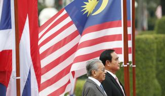 Malaysian Prime Minister Mahathir Mohamad, front, and Thailand's Prime Minister Prayuth Chan-ocha listen to their national anthems during a welcoming ceremony at the government house in Bangkok, Thailand, Wednesday, Oct. 24, 2018. Mahathir on Wednesday began a two-day visit to Thailand during which he's expected to discuss peace talks in southern border provinces with Malaysia, where a Muslim separatist insurgency has been raging for over a decade. (AP Photo/Sakchai Lalit, Pool)