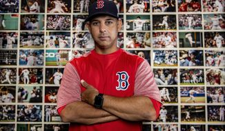 In this Oct. 2, 2018 photo provided by the Boston Red Sox, manager Alex Cora poses in his office during before the American League Division Series in front of a wall of photographs depicting every win throughout the season. (Billie Weiss/Boston Red Sox via AP)