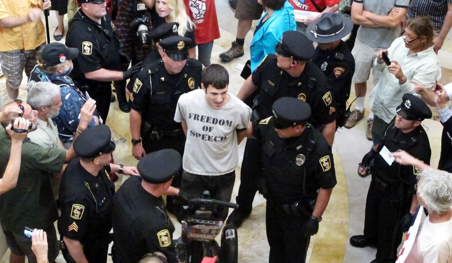 Jeremy Ryan, of Madison, is led away by Capitol police as part of a crackdown on people who gather daily in the Capitol without a permit to sing protest songs on Thursday, July 25, 2013, in Madison, Wis. (AP Photo/Scott Bauer)
