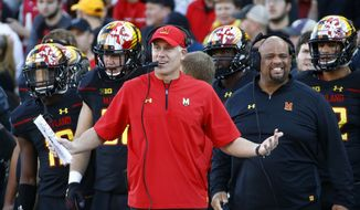 FILE - In this Saturday, Oct. 14, 2017, file photo, Maryland head coach DJ Durkin, center, reacts on the sideline during the first half of an NCAA college football game against Northwestern in College Park, Md. Playing in a bowl game would be a remarkable achievement for Maryland. Offensive coordinator Matt Canada is serving as interim coach while Durkin is on administrative leave, pending the result of an investigation of the football program. (AP Photo/Patrick Semansky, File) **FILE**