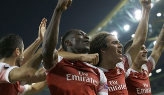 Teammates celebrate with Arsenal's Danny Welbeck, center left, who scored his side's first goal during the Europa League group E soccer match between Sporting CP and Arsenal at the Alvalade stadium in Lisbon, Thursday, Oct. 25, 2018. (AP Photo/Armando Franca)