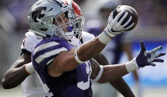 FILE - In this Saturday, Oct. 13, 2018, file photo, Kansas State running back Alex Barnes (34) catches a Skylar Thompson pass while covered by Oklahoma State linebacker Calvin Bundage, back, during the second half of an NCAA college football game in Manhattan, Kan. This season, four Big 12 backs are averaging at least 100 yards rushing per game in conference action.(AP Photo/Orlin Wagner, File)