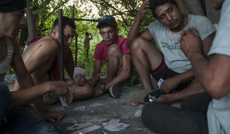 Honduran migrants walking in a caravan that aims to reach the U.S., play cards near San Cristobal Acasaguastian, about 67 miles northeast of Guatemala City, Guatemala, Wednesday, Oct. 24, 2018. This new group of a few hundred Honduran migrants are behind the first caravan of Central American migrants that has swelled to thousands and is currently traveling through Mexico. (AP Photo/Oliver de Ros)