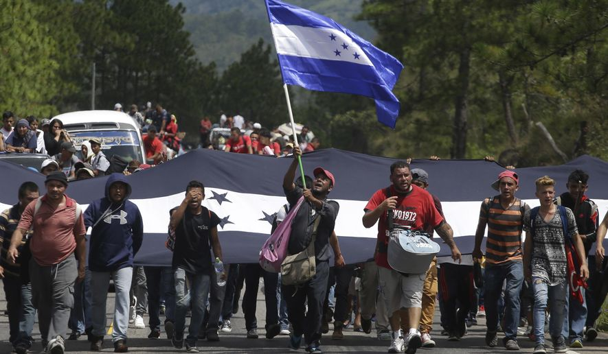 Hondurans march in a caravan of migrants moving toward the country's border with Guatemala in a desperate attempt to flee poverty and seek new lives in the United States, in Ocotepeque, Honduras, on Monday, Oct. 15, 2018. (AP Photo/Moises Castillo)