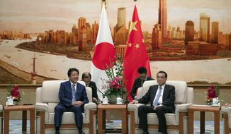 Chinese Premier Li Keqiang, right, and Japanese Prime Minister Shinzo Abe meet at the Great Hall of the People in Beijing, Thursday, Oct. 25, 2018. Abe arrived in Beijing on Thursday as both countries try to repair ties that have been riven by disputes over territory, military expansion in the Pacific and World War II history. (Roman Pilipey/Pool Photo via AP)