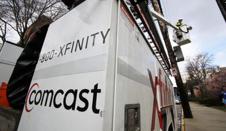 FILE- In this March 27, 2017, file photo, a Comcast worker performs work in Pittsburgh. Comcast Corp. reports earnings Thursday, Oct. 25, 2018. (AP Photo/Gene J. Puskar, File)