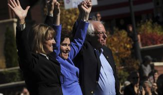 Senator Bernie Sanders, right, campaigns for Nevada Democrats U.S. Rep. Jacky Rosen, middle, and Kate Marshall, Democratic candidate for Nevada lieutenant governor, on the University of Nevada, Reno campus on Thursday, Oct. 25, 2018. (Jason Bean /The Reno Gazette-Journal via AP)