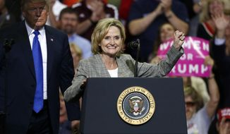 FILE - In this Oct. 2, 2018 photograph, President Donald Trump stands in the shadows while U.S. Sen. Cindy Hyde-Smith, R-Miss., encourages the crowd at a rally in Southaven, Miss. Candidates and political action committees are increasing advertising ahead of the crowded Nov. 6 special election for a U.S. Senate seat in Mississippi. (AP Photo/Rogelio V. Solis, File)