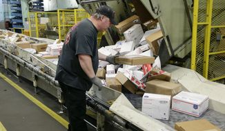 FILE - In this Dec. 14, 2017 file photo, Steve Robino arranges packages on a conveyor belt at the main post office in Omaha, Neb. The shipment of several pipe bombs to CNN and several prominent Democrats raises fresh questions about mail safety and what measures the U.S. Postal Service and private delivery services take to prevent explosives and other illegal substances from entering into the mail. (AP Photo/Nati Harnik, File)
