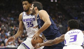 Sacramento Kings guard Yogi Ferrell, right, hits the ball out of the hands of Memphis Grizzlies forward Omri Casspi, center, as he drives against Sacramento Kings forward Marvin Bagley III, left, during the first quarter of an NBA basketball game Wednesday, Oct. 24, 2018, in Sacramento, Calif. (AP Photo/Rich Pedroncelli)