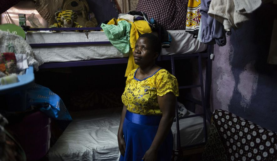 """Margaret Oliele, former detained patient, poses for a portrait in her home in Nairobi, Kenya. During a botched cesarean section in 2010, doctors left a pair of surgical scissors inside her stomach; a second surgery was needed to remove the scissors and she later suffered a ruptured bladder and a blood infection. When she couldn't pay her hospital fees, Oliele was taken to a detention ward. """"I tried to escape, but when I got to the main gate, I was taken by the security guards."""" (AP Photo/Bram Janssen)"""