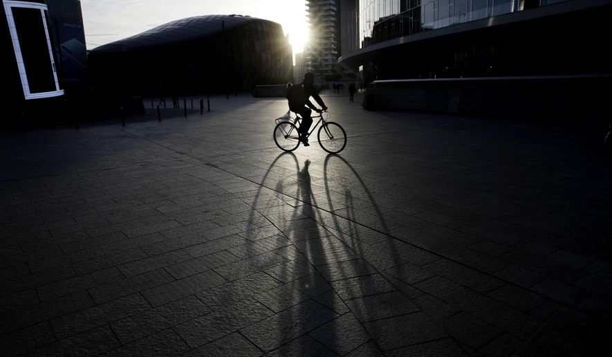 A man rides a bike in the early morning at the Porta Nuova business center in Milan, Italy, Wednesday, Oct. 24, 2018. (AP Photo/Luca Bruno)