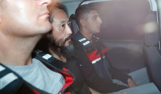 Japanese journalist Jumpei Yasuda, center, is driven out of the immigration center in Antakya, Turkey, Wednesday, Oct. 24, 2018. Yasuda was freed after more than three years of captivity in Syria Wednesday. (Yosuke Mizuno/Kyodo News via AP)