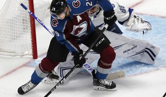 Colorado Avalanche center Nathan MacKinnon, front, tries to redirect the puck as Tampa Bay Lightning goaltender Andrei Vasilevskiy defends the net in the first period of an NHL hockey game, Wednesday, Oct. 24, 2018, in Denver. (AP Photo/David Zalubowski)