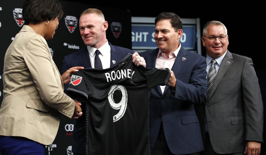 FILE - In this Monday, July 2, 2018, file photo, District of Columbia Mayor Muriel Bowser, left, shakes hands with English soccer star Wayne Rooney, as he holds up his new jersey next to MLS team D.C. United Managing Partner and CEO Jason Levien, and Dave Kasper, general manager and vice president of soccer operations, right, during a news conference announcing Rooney's signing with the club, at the Newseum in Washington. Rooney and his American club are headed to the Major League Soccer playoffs. (AP Photo/Jacquelyn Martin) ** FILE **