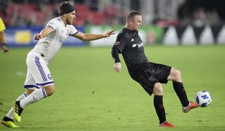 FILE - In this Sunday, Aug. 12, 2018, file photo, D.C. United forward Wayne Rooney, right, kicks the ball against Orlando City midfielder Dillon Powers during the second half of an MLS soccer match, in Washington. English striker Rooney and his American club are headed to the Major League Soccer playoffs. (AP Photo/Nick Wass, File)