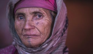 In this Saturday, Oct. 13, 2018 photo, Etto Elchafai, 63, poses for a portrait displaying her face tattoo, in the Middle Atlas town of Tinguerf, near Azilal, central Morocco. (AP Photo/Mosa'ab Elshamy)