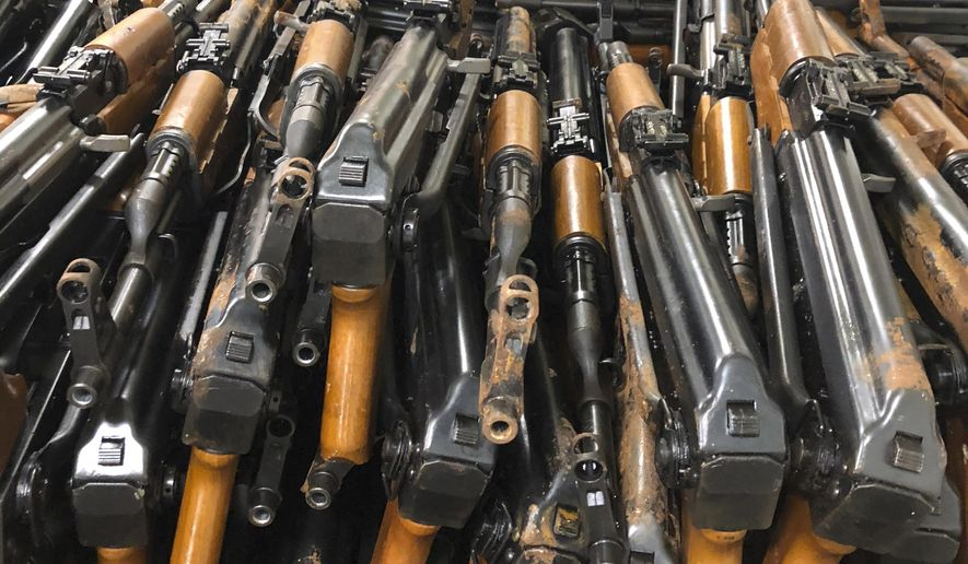 A pile of assault weapons sits jammed into a corner below the deck of the guided-missile destroyer USS Jason Dunham on Wednesday, Oct. 24, 2018. The weapons, seized at the end of August, were inspected by U.N. officials Thursday, Oct. 25, to determine what country they came from. (AP Photo/Lolita Baldor)