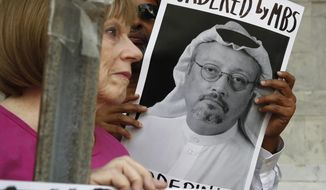 FILE - In this Oct. 10, 2018, file photo, people hold signs during a protest at the Embassy of Saudi Arabia about the disappearance of Saudi journalist Jamal Khashoggi, in Washington. Saudi Arabia's financial clout among the Arab media has given it an influential tool as it grapples with the international outcry first over the disappearance and later the death of Saudi writer Jamal Khashoggi. From the time he vanished into the kingdom's consulate in Istanbul, Riyadh's allied newspapers and TV stations across the region echoed the Saudi denial of any knowledge of his fate or weaved alternative scenarios of an alleged plot by rivals Qatar and Turkey to destabilize the kingdom. (AP Photo/Jacquelyn Martin, File )