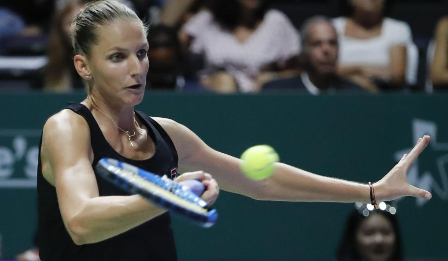 Karolina Pliskova of the Czech Republic plays a return shot while competing against Petra Kvitova of the Czech Republic during their women's singles match at the WTA tennis finals in Singapore, Thursday, Oct. 25, 2018. (AP Photo/Vincent Thian)