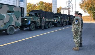 In this photo provided by South Korea Defense Ministry, a U.S. and a South Korean army soldiers stand before leaving from the border village of Panmunjom, South Korea, Thursday, Oct. 25, 2018. The rival Koreas and the U.S.-led U.N. Command completed withdrawing firearms and troops from a jointly controlled area at the Koreas' border village on Thursday as part of their sweeping agreements to reduce decades-long military animosities on the Korean Peninsula. (South Korea Defense Ministry via AP).